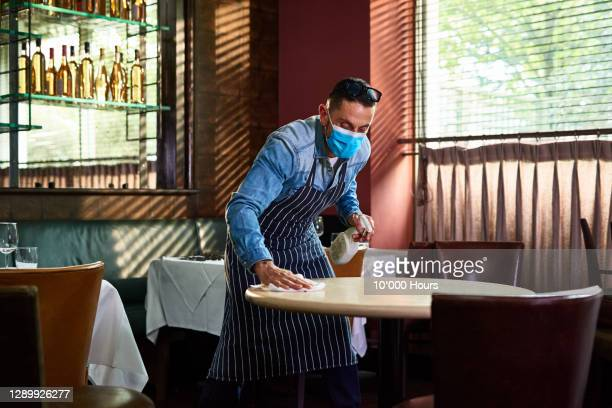 man cleaning restaurant table with disinfectant - restaurant stock pictures, royalty-free photos & images