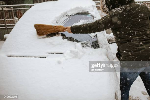 man cleaning snow from car - extreme weather stock photos and pictures
