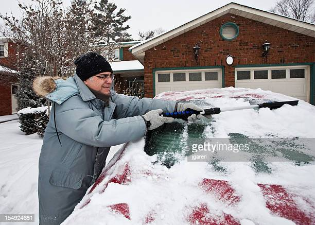 Man Cleaning Snow Off Car