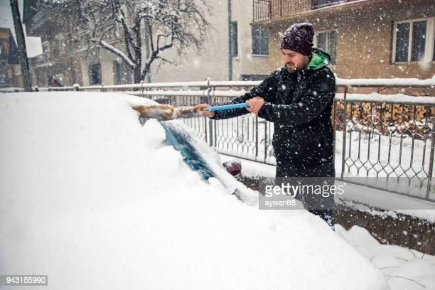 man cleaning snow off car - scraping stock photos and pictures