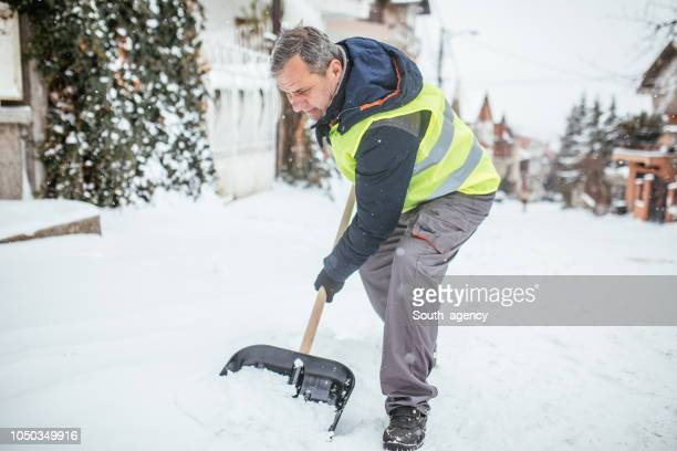 man cleaning snow on the street - absence stock pictures, royalty-free photos & images