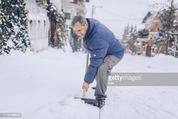 man cleaning snow on the street - snow shovel stock photos and pictures