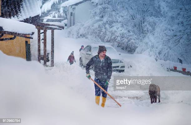 man cleaning snow with shovel - extreme weather stock photos and pictures