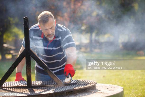 man cleaning the barbeque - metal grate stock photos and pictures