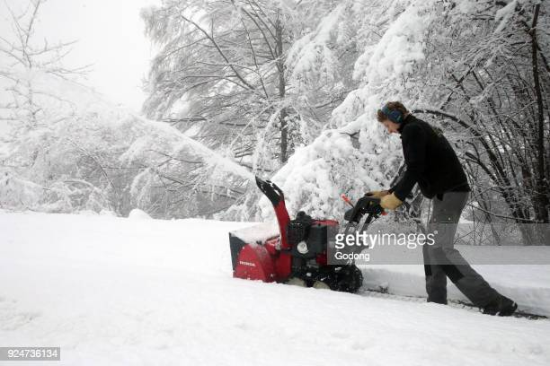 Man cleaning the snow with a snowblower France