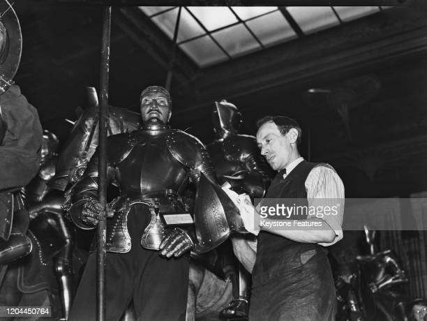A man cleaning the suits of armour at the Tower of London in London England July 1940