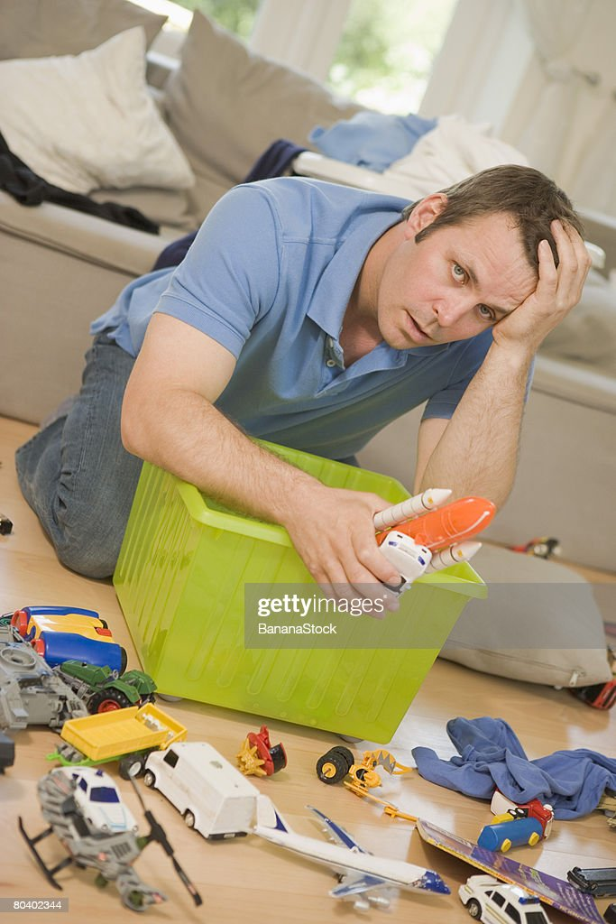 Man cleaning up toys : Stock Photo