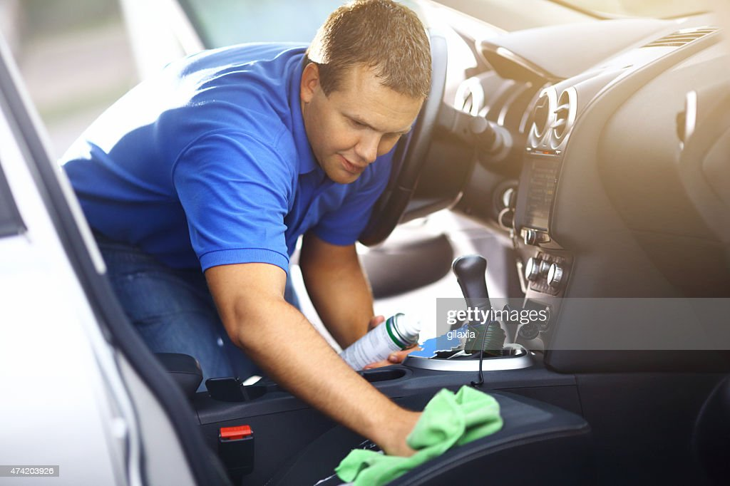 Man cleaning upholstery of his vehicle. : Stock Photo
