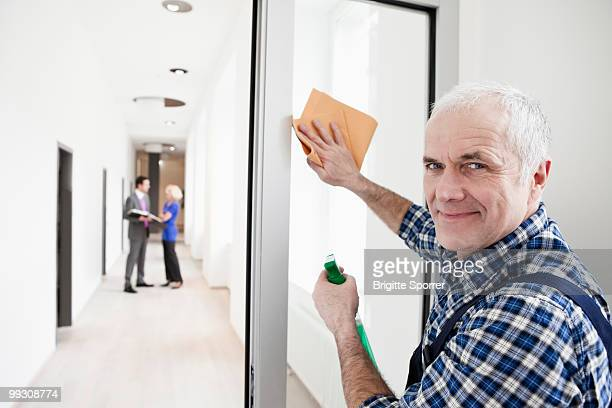man cleaning window - janitor stock photos and pictures