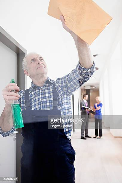 man cleaning window - janitorial services stock photos and pictures