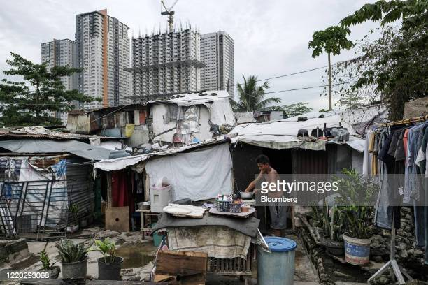 Man cleans a cooking pot outside his home in the San Roque neighborhood as commercial high-rise buildings stand in the background in Quezon City,...