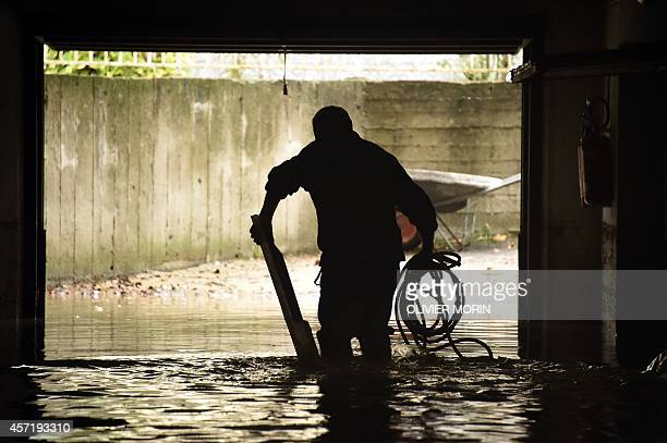 A man cleans a flooded basement following heavy rain in Gavi on October 14 2014 Northern Italy has been hit by heavy rain and wind in the last 48...