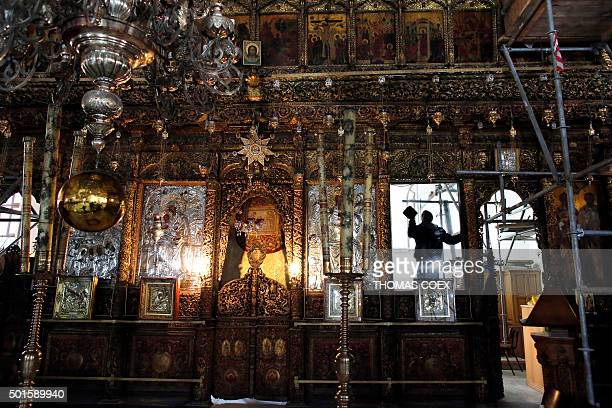 A man cleans a part of the Greek Orthodox altarpiece inside the Church of the Nativity revered as the site of Jesus Christ's birth on December 16...