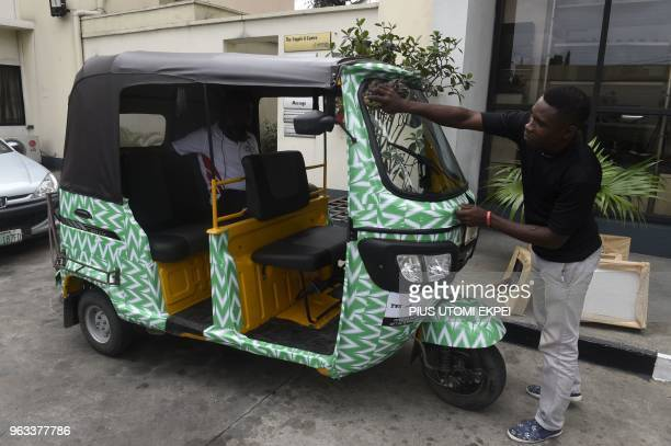 A man cleans a rickshaw branded in Nigerian team jersey in southern city of Port Harcourt on May 28 2018 Nigeria will take on DR Congo as part of...