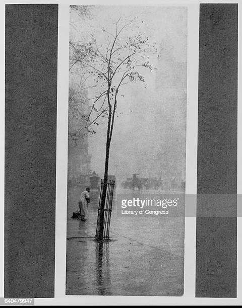 A man cleans a wet New York City street in The Sweeper by Alfred Stieglitz