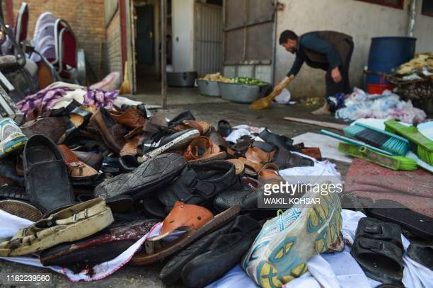 A man cleans an area next to a pile of shoes and sandals of victims outside a wedding hall after a deadly bomb blast in Kabul on August 18 2019 More...
