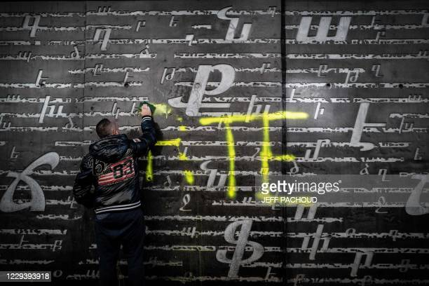 Man cleans an outside wall of the National Armenian Memorial Centre in Decines-Charpieu, near Lyon, on November 1, 2020 where pro-Turkish yellow...