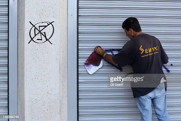Man cleans anti-far right political graffiti from the exterior of a bank ahead of Sunday's general election on June 14, 2012 in Athens, Greece. The...