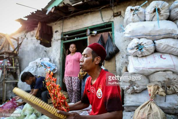 A man cleans chilli for sale at a traditional market in Jakarta Indonesia on July 7 2019