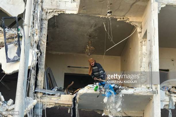 TOPSHOT A man cleans debris in the aftermath of an explosion at a base for Asian jihadists in a rebelheld area of the northwestern Syrian city of...