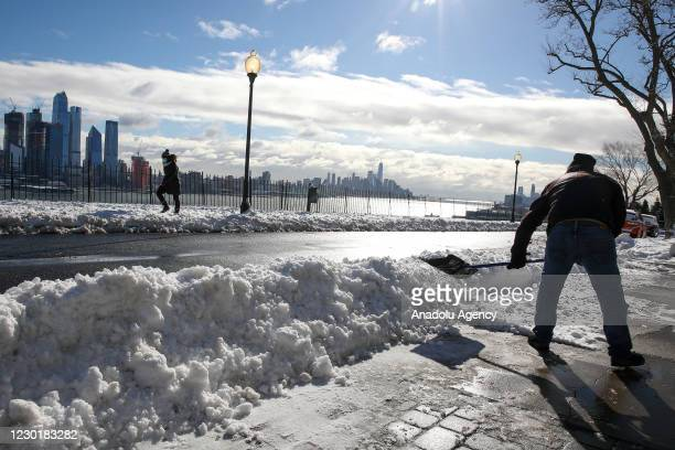 Man cleans his driveway in neighborhood of Weehawken, New Jersey, United States on December 17, 2020.