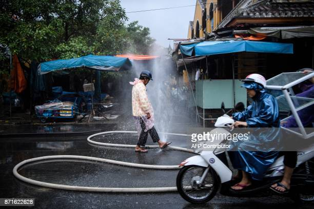 A man cleans his feet with a burst water pipe in the town of Hoi An on November 8 2017 following days of heavy rains after Typhoon Damrey hit the...