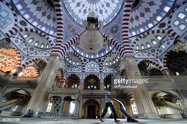 A man cleans inside the Heart of Chechnya Akhmad Kadyrov Mosque one of the largest mosques in Russia in central Grozny on July 26 2017 / AFP PHOTO /...