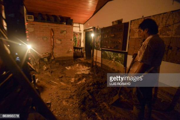 TOPSHOT A man cleans mud out of his store which was damaged by mudslides following heavy rains in Mocoa Putumayo department southern Colombia on...