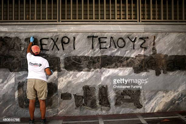 Man cleans off the latest batch of anti-austerity graffiti from the walls of the Bank of Greece on July 14, 2015 in Athens, Greece. Greek Prime...