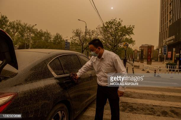 Man cleans sand and dirt off his car after a short rainfall during a sandstorm in Beijing on April 15, 2021.