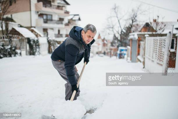 man cleans sidewalk in winter - deep snow stock pictures, royalty-free photos & images