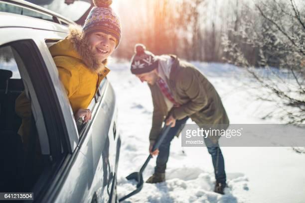 Man reinigt Schnee in der Nähe das Auto in der Natur