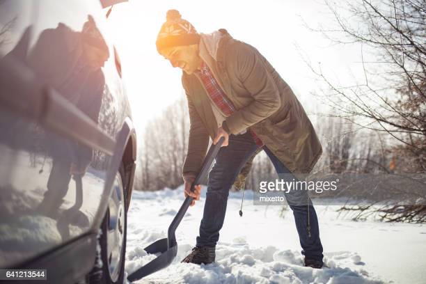 Man cleans snow near the car with shovel in nature
