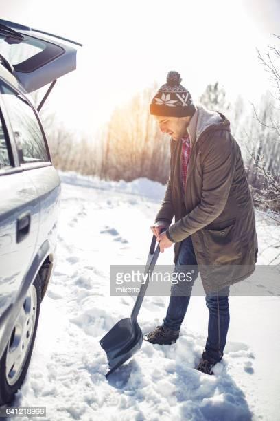 Man cleans snow near the car with shovel