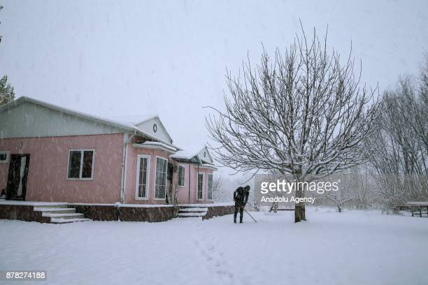 A man cleans snow off in front of his house after heavy snowfall in Van Turkey on November 24 2017