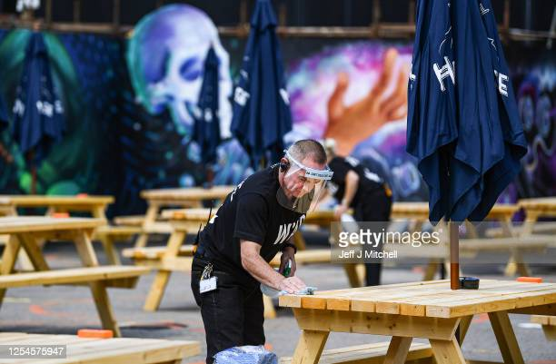 Man cleans tables as members of the public enjoy their first drink in a beer garden at SWG3 on July 06, 2020 in Glasgow, Scotland. Beer gardens...