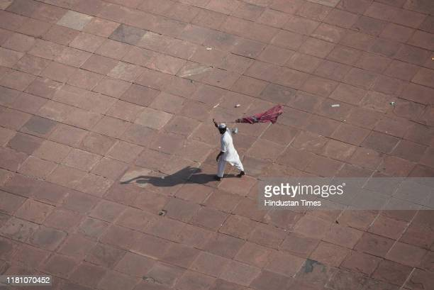 A man cleans the flooring of Jama Masjid on the day of the Supreme Court verdict in the Ram Janmabhoomi Babri Masjid case on November 8 2019 in New...