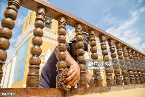 A man cleans the handrail of Trujillo Cathedral prior Pope Francis 4day apostolic visit to Peru on January 18 2018 in Trujillo Peru