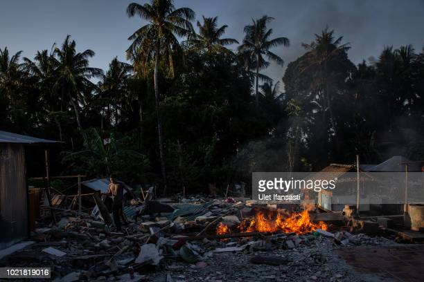A man cleans the ruins of their damaged houses in Pemenang on August 23 2018 in Lombok island Indonesia Thousands of residents remain stranded at the...