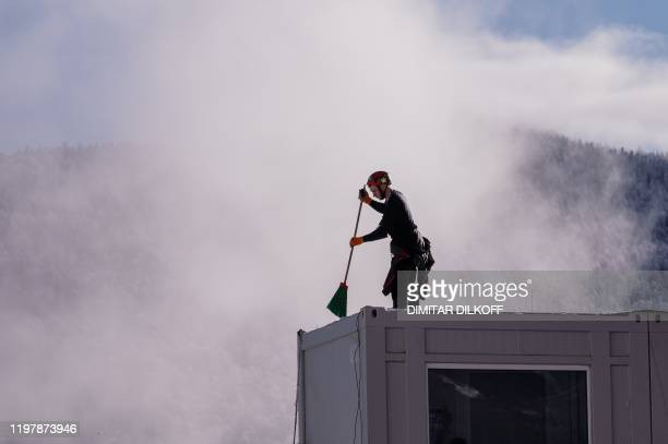 Man cleans the snow from the roof of the media tribune after the downhill events of the Women's Alpine Skiing World Cup were cancelled due to the...