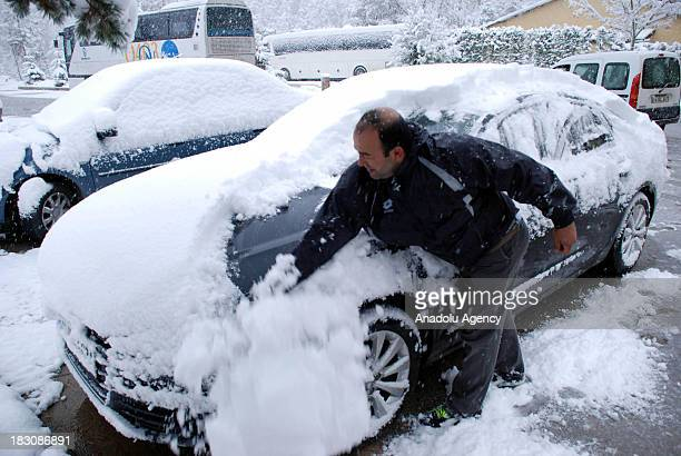 A man cleans the snow off his car on October 4 2013 in Abant Nature Park Turkey The recent cold front sweeping across Turkey as a result of the low...