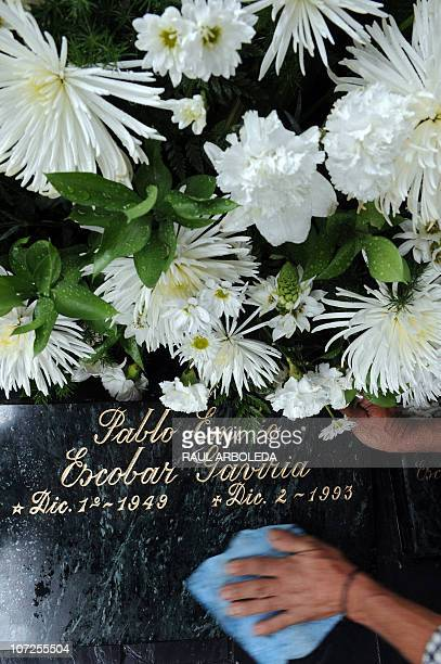 A man cleans the tombstone of Colombian drug lord Pablo Escobar at Montesacro cemetery on December 2 2010 in Medellin Antioquia department Colombia...