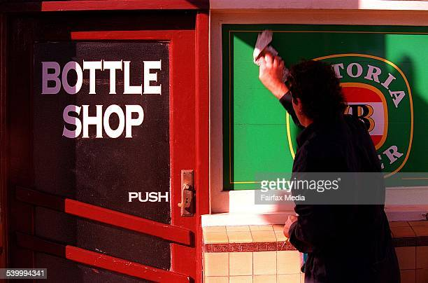 A man cleans the windows of a small bottle shop 13 May 2002 AFR Picture by JAMES DAVIES