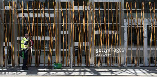 A man cleans the windows of the Scottish Parliament building in Edinburgh Scotland on June 27 2016 British leaders battled to calm markets and the...