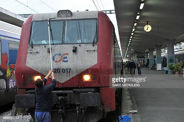 A man cleans the windows of the train to Bulgaria in the railway station of Thessaloniki on 10 May 2014 Greeces rail operator TRAINOSE will resume...