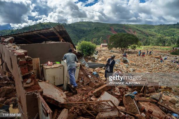 A man cleans up a destroyed house on March 19 2019 in Chimanimani as a hundred houses were damaged by the Cyclone Idai More than a thousand people...