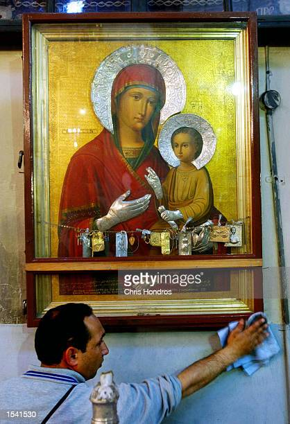 A man cleans up a Greek Orthodox icon portrait of Mary and Jesus in the Church of the Nativity May 11 2002 in Bethlehem in the West Bank Clergy and...