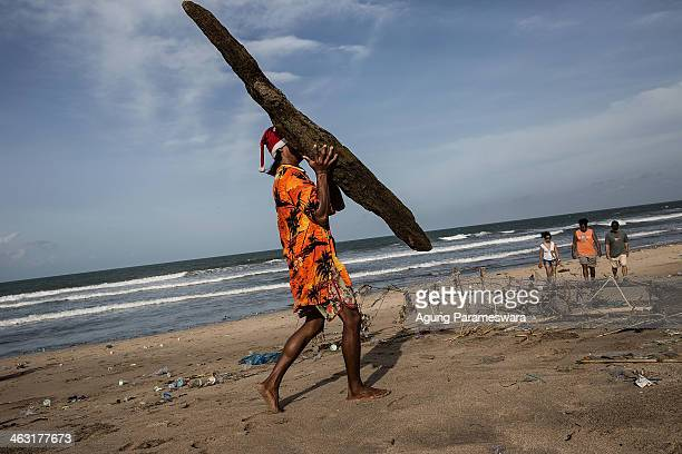 A man cleans up piles of the debris brought in by strong waves at Kuta Beach on January 17 2014 in Kuta Indonesia The sight of trash washed up on...
