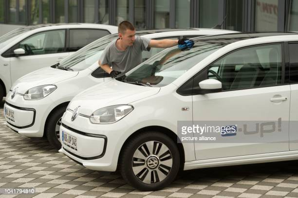 Man cleans windscreen of a Volkswagen eup Wolfsburg Germany 04 September 2013 With the eup Volkswagen gets into the business of the oure electric...