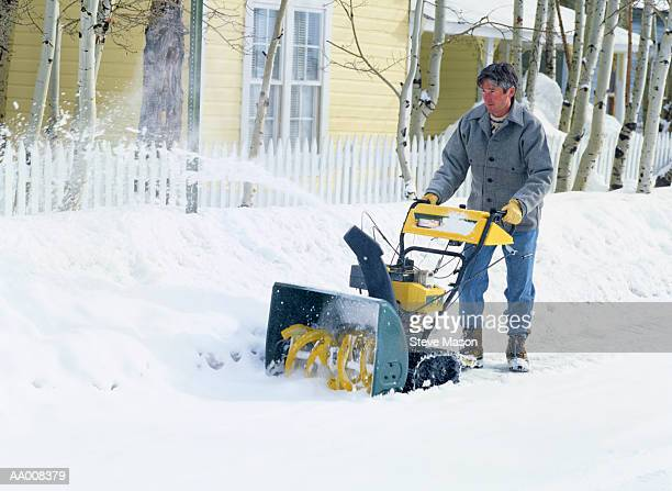 Man Clearing a Sidewalk with a Snowblower